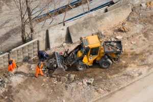 workers and machine conducting a site clearance